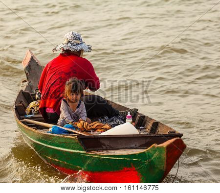 Tonle Sap Lake Siem Reap, Cambodia - OCTOBER 13, 2012: Asian woman floating on a boat with beautiful little girl. The life of the local residents