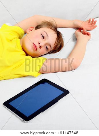 Tired Kid with Tablet Computer on the Bed