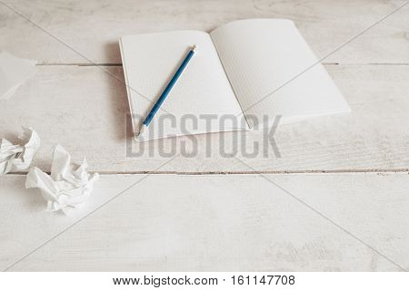 Blank copybook with pencil on table, free space. Writer, artist, journalist workplace with empty notebook and paper wads. Lack of inspiration, creativity, deadline concept