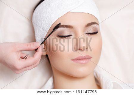 Permanent makeup. Beautiful young woman gets eyebrow correction procedure. Young woman tweezing her eyebrows in beauty saloon. Young woman plucking eyebrows with tweezers close up poster