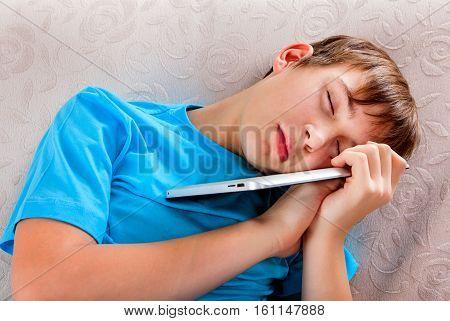 Tired Teenager sleep with Tablet Computer on the Sofa