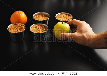 Man's hand adding an apple to an arrangement of four steel pans with apple crumble dessert and one orange on shiny black table