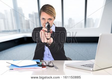 young attractive businesswoman sitting at computer desk pointing gun in powerful boss attitude and killer employee concept tired of working at modern business district office