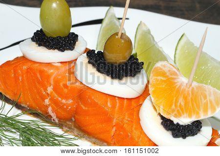 Smoked salmon garnished with egg orange olive grape lemon and caviar on a plate