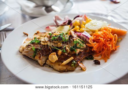 roasted white fish with garlic and parsley served with fresh vegetables