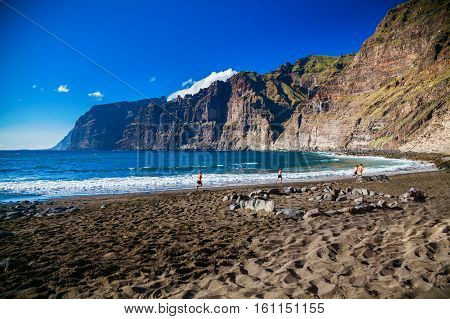 beach Playa de los Guios in Los Gigantes with four running men Tenerife Canary Islands Spain