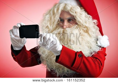 Man weared Santa's mascarade costume for cristmas, taking photo or video on his mobile device, pressing screen with his finger. Focus on smartphone, close up shot, isolated on red