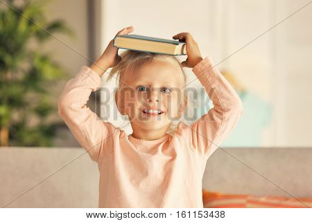 Small girl plying with book at home