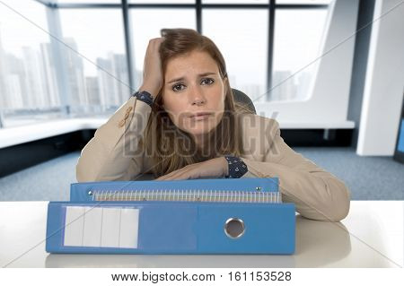 young attractive sad and desperate businesswoman suffering stress and headache at desk looking worried depressed and overwhelmed at business district modern office