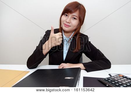Smiling businesswoman holding thumps up at office with calculator documents and file