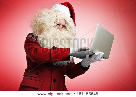 Santa in white gloves quickly types mail or programming code on his portable laptop, hacking web site and fixing bugs. isolated on red background Computer repairing or programming holiday concept
