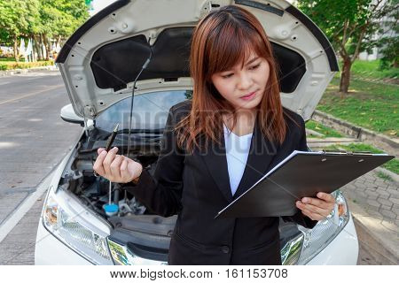 Insurance agent examining car after accident holding a pen and thinking of car breakdown for writing on document