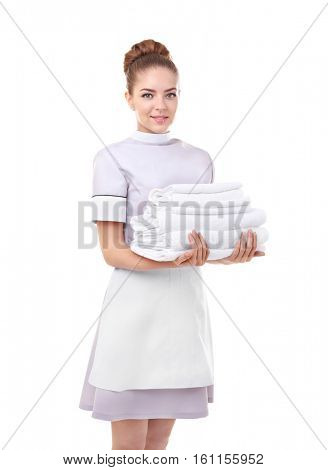 Beautiful chambermaid holding pile of clean towels on white background