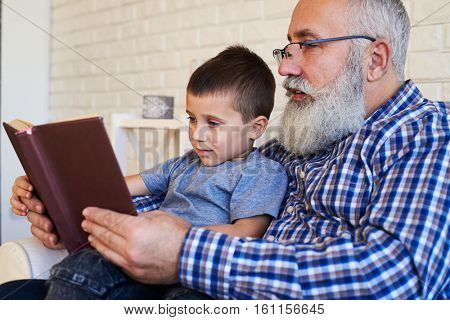 Mid shot of a senior grandfather and his grandson reading attentively an interesting book. An elderly smiling male reading a book