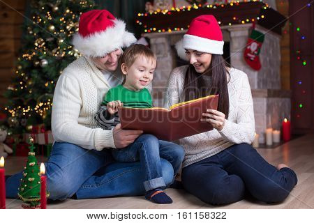 family, christmas, x-mas, concept - smiling parents in santa hats and kid reading book