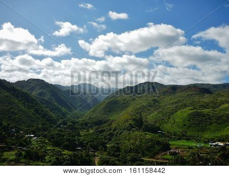 green mountain landscape with fluffy white clouds