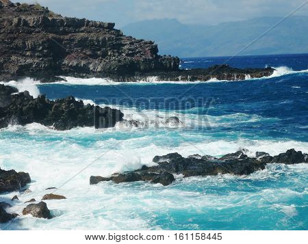 crashing ocean waves with rocky cliff in the background