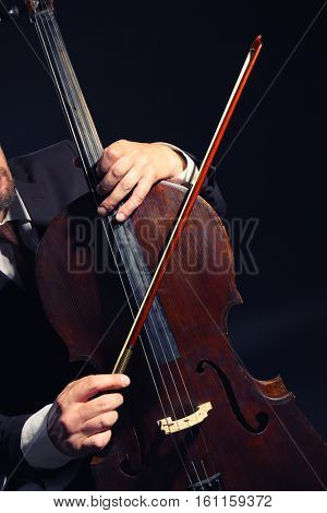 Man playing cello in darkness, closeup