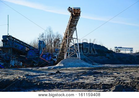 conveyor with piles of gravel in a granite quarry