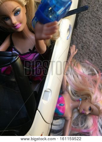 Public Service Announcement: Don't Selfie and Drive concept with a Barbie doll running over another Barbie doll while distracted driving