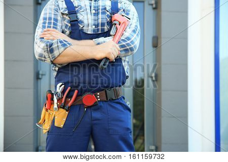 Plumber with pipe wrench against glass door, close up view