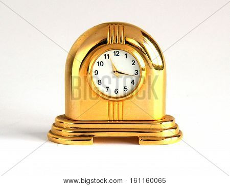 Retro gilded table clock on white background with shadows