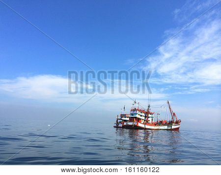 Two little fishing boats moored in the middle of blue turquoise ocean on the sunny clear sky day
