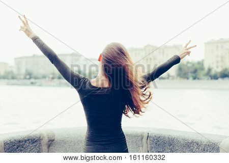 Young woman standing with her back raised his hands, and show victory sign, once free from the city and work. Freedom. Escape. Victory. Conquest. Outdoor.