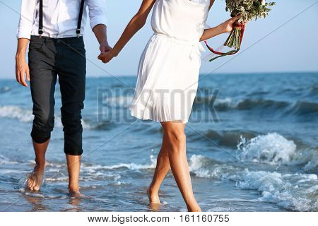 Young happy couple with flowers walking on seashore