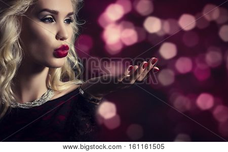 Beautiful blond woman blowing on his hand on background of festive lights.