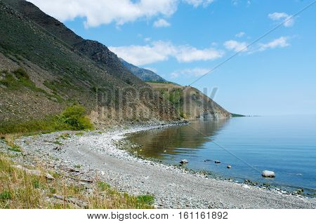 Baikal stony beach with sun and blue water, Russia