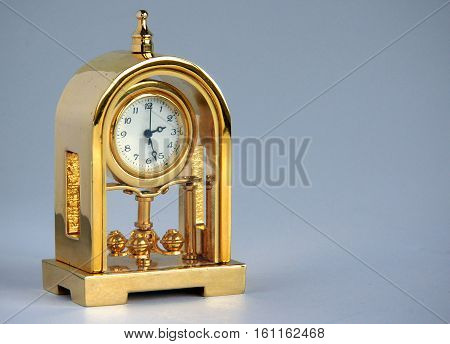 Retro gilded table clock on blue gray background