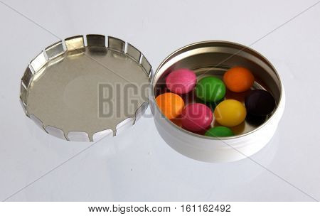 Metallic silver pillbox with color pills on white