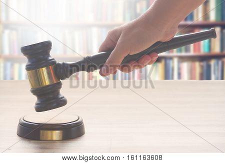 someones hand holding Wooden Law Gavel over wooden table against bookshelves