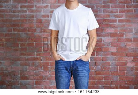 Young man in blank white t-shirt standing against brick wall, close up