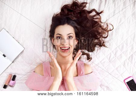 Excited brunette enjoying good news top view. Happy woman in pink clapping on bed, smiling at camera. Fun, joy, happiness, surprise concept