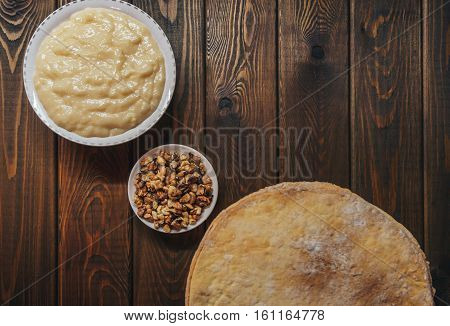 Ingredients for baking a cake, top view on wooden board. shortcakes, buttercream or cream and nuts on a plate on vintage wooden kitchen table. copyspace for cook recipe.