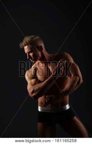Sexy blond bodybuilder in black and white shorts posing in profile in studio