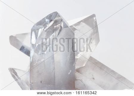 Cluster of several transparent quartz crystals close-up on a white background