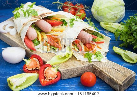 Hot dog - sandwich with sausage in pita, Korean carrots, tomatoes, onions, parsley and pepper