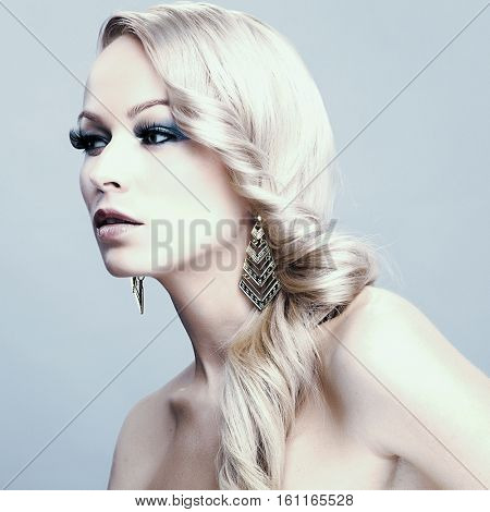 Beautiful blond woman. Pretty girl with long hair. Jewelry and Beauty. Fashion art photo