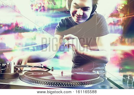 Club DJ playing mixing music on vinyl turntable at party