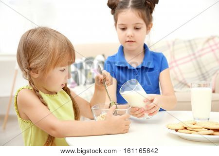 Two little girls with milk and cornflakes