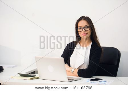 Young pretty business woman with notebook in the office.
