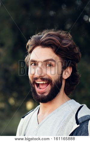 Widely smiling man close-up. Portrait of young bearded guy looking at camera with sly look. Joy, joke, fun, leg-pull, stand-up concept