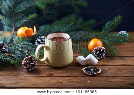 mug with hot chocolate, christmas tree, tangerines and marshmallow on a wooden background. Dark photo. Empty space for text
