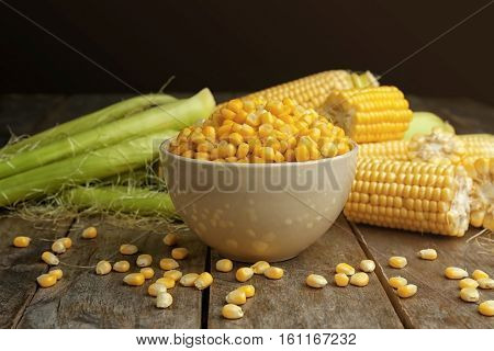 Bowl with corn seeds and ripe corn cobs on wooden table