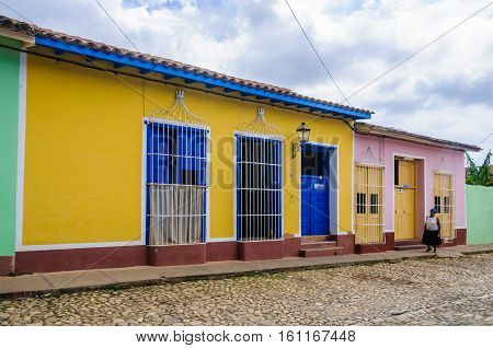TRINIDAD, CUBA - MARCH 23, 2016: Yellow house with blue door and windows on the cobblestone streets in the UNESCO World Heritage old town of Trinidad Cuba