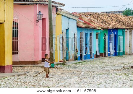 TRINIDAD, CUBA - MARCH 23, 2016: Local kid playing on the cobblestone street in the UNESCO World Heritage old town of Trinidad Cuba