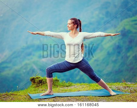 Yoga outdoors - sporty fit woman doing Ashtanga Vinyasa Yoga asana Virabhadrasana 2 Warrior pose posture in mountains. Vintage retro effect filtered hipster style image.